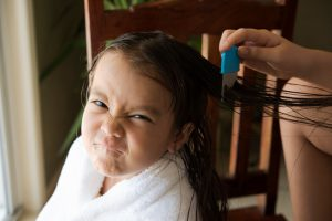 a girl is upset face, her mother do head lice treatment.